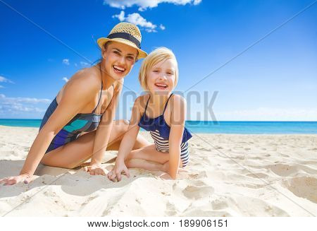 Smiling Young Mother And Daughter In Swimwear On Seacoast