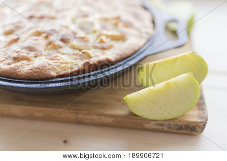 Freshly baked apple pie in black form for baking and slices of fresh green apples on a light bamboo cutting board