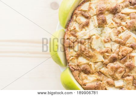 A fresh baked apple pie surrounded by lobules of fresh green apples stands on a light wooden background in the right part of the frame.