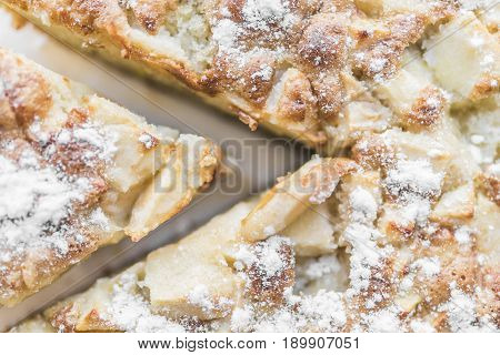 Apple pie and a cut piece of pie are sprinkled with powdered sugar and lie on a white plate close-up view