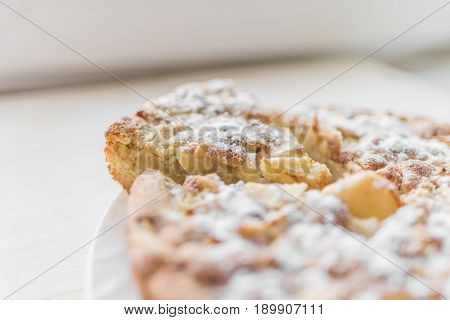 A fresh baked apple pie and a cut piece are sprinkled with sugar powder and lie on a white plate on a light background.