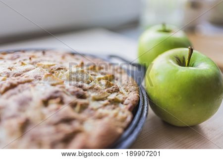 Freshly baked apple pie in a black baking sheet and two fresh green apples on a light wooden background