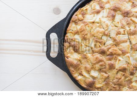 Apple pie in a black baking tray with handles stands on a light wooden background in the right side of the frame.