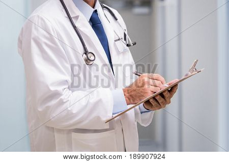 Close up of hands of senior doctor writing on a clipboard at hospital. Doctor with a stethoscope around his neck holding a clipboard in the hallway of a medical clinic.