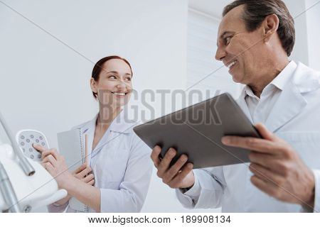 Good for you. Smiling female intern standing opposite her mentor and holding notes in right hand while pressing the button on control panel