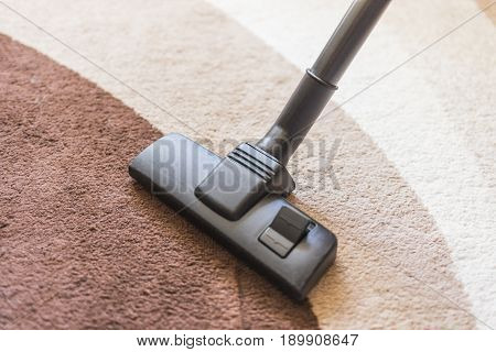 A vacuum cleaner with a black brush cleans the carpet with a dark and light brown pattern.