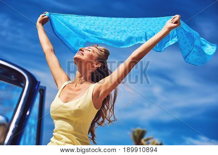 Happy woman with a hands raised against blue sky. Idyllic scenery