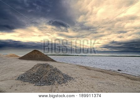 River port with a sandy heap. Cloudy sky.