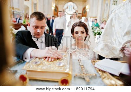 Wedding Couple At Church Swear Allegiance Each Other Holding Hands On Gospel.