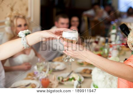 Woman gives a glass with champagne to someone over the table