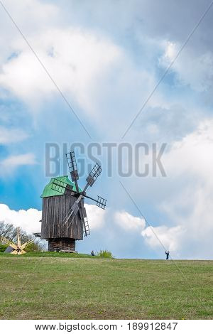 Kyiv Ukraine - April 23 2017: Ancient traditional wooden windmill beautiful spring landscape with sky. National architecture. Kyiv Ukraine - April 23 2017: Ancient traditional wooden windmill beautiful spring landscape with sky. National architecture. Nat