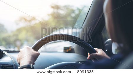Woman holding on black steering wheel while driving a car with traffic background