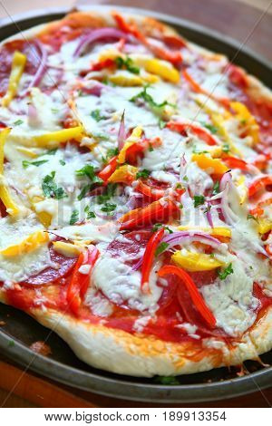 Pizza with salami onion red and yellow bell peppers and mozzarella cheese