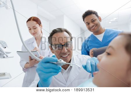 Open your mouth. Responsible intern making notes while observing the process of treatment and standing on the background