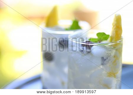 Two glasses of white wine cocktails with fresh pineapple blueberries and mint with room for text