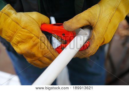 Handyman with work gloves makes a cut in a piece of plastic piping.