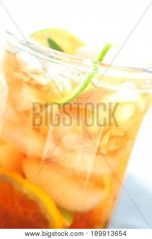 Closeup of a glass of iced tea with lime and lemon slices over ice