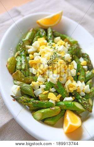 Asparagus with chopped boiled egg and lemon wedges from overhead