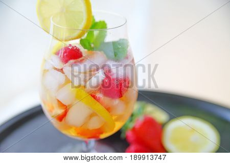 Wine cocktail with fresh berries lemon and mint over ice