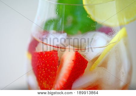 Closeup of wine cocktail with fresh berries lemon and mint leaves