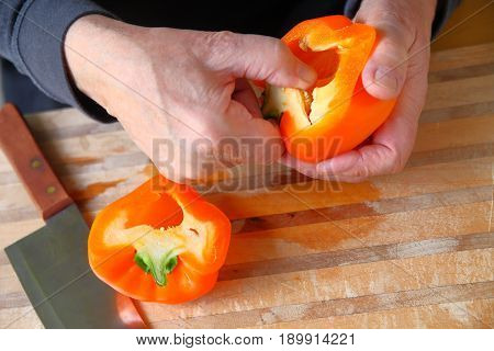 A man removes seeds from an orange-colored bell pepper over a cutting board with copy space