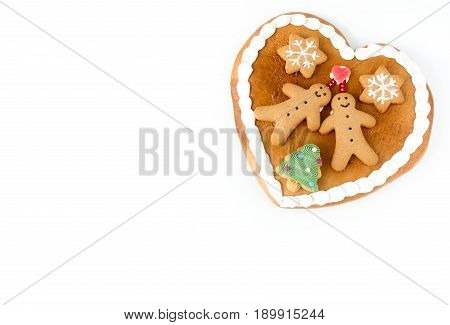 Close up of a cute Gingerbread heart decorated with Gingerbread Men Gingerbread Stars and a Christmas Tree Cookie on white background with lots of copy space.