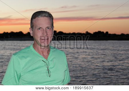 Happy mature caucasian male standing in front of a lake with a beautiful evening sky. Cheerful guy closeup in front of water with an orange pink sunset outdoors.