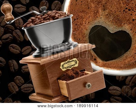 Coffee grinder and cup of coffee on the coffee beans background. Abstract, concept.