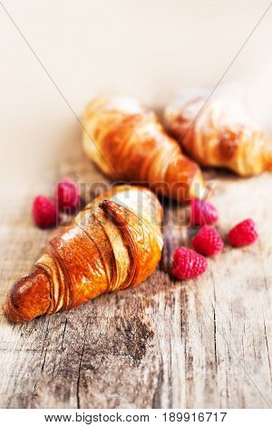 Fresh croissants with berries on a table. Tasty golden croissants on dark brown wooden background