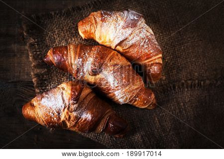 Fresh croissants on a table close up. Tasty golden croissants on dark brown wooden background macro