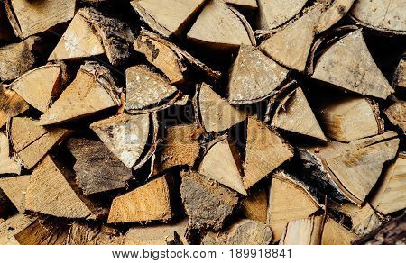 Natural wooden background selective focus closeup. Firewood texture background. Chopped firewood stacked and prepared for winter. Pile of wood logs. Firewood on a stack