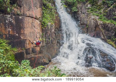 Climber In The Background Of Beautiful Cascading Datanla Waterfall In The Mountain Town Dalat, Vietn
