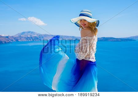 Woman enjoying warm summer weather with blue skirt blowing in the wind
