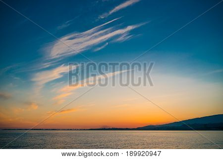 Sunset on the background of bright blue sky with white Cirrus clouds on a background of calm sea