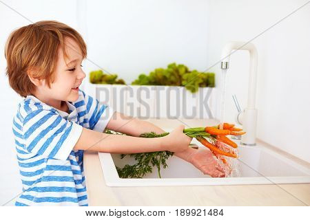 Cute Young Boy Washing The Carrots Under Tap Water In The Kitchen