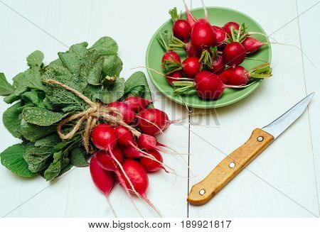Bunch Of Fresh Organic Red Radishe With Tops And Green Leaves Near Plate With Radish And Knife On Wh