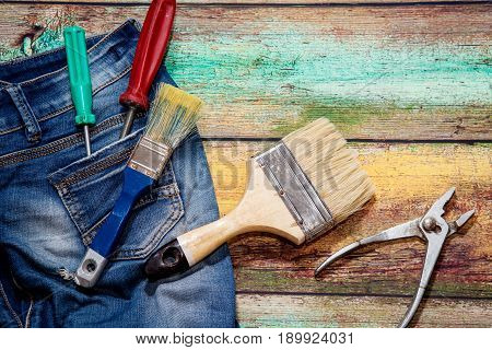 Two screwdrivers in the concept pocket of jeans, brushes and pliers on a wooden background for work days