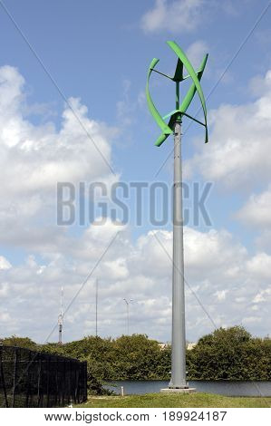 Green color power generating wind turbine near a park lake. Unusual vertical access wind turbine outside in Mills Pond Park.