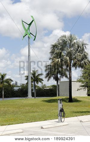 Fort Lauderdale FL USA - May 16 2017: Urban wind turbine with an EV charging center. Electric vehicle charging center with a wind turbine.