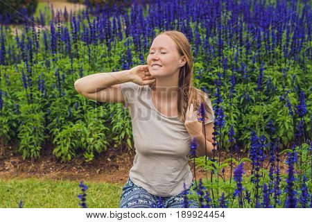 Young Woman On The Background Of Blue Salvia Farinacea Flowers Blooming In The Garden