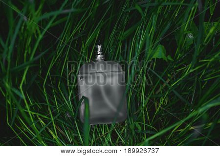 male bottle of perfume over green background