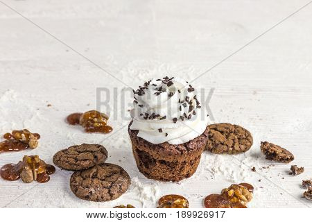 Confectionery basket with caramel and nuts, capcake with creamy cream, biscuits and caramel on a white wooden background
