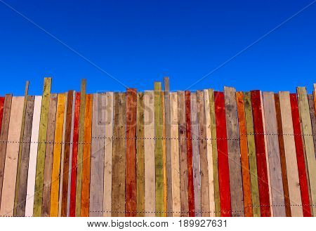 Multicolored wooden wall and blue sky. A colored wall of wood with a lot of copy space. Wooden fence and blue sky.