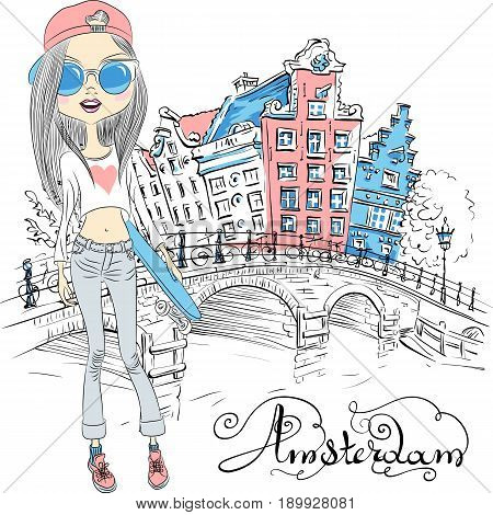 Fashionable hipster girl tourist with skateboard near the bridge on the Amsterdam street with traditional Dutch houses, Holland, Netherlands.