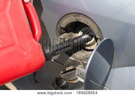 Refilling fuel from a plastic canister. Car breakdown. No fuel. Adding fuel.