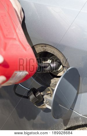 Add fuel from a plastic canister to the car's tank.