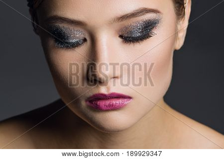 Portrait of a young woman with a glamorous make-up.