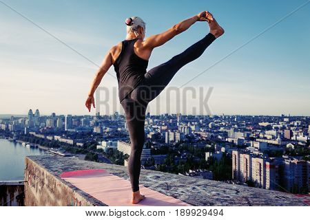 Portrait Of Beautiful Blonde Strong Woman In Sportwear Doing Workout Stretching On The Roof Of A Sky