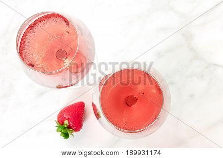 A high-key overhead photo of two glasses of rose wine with strawberries, on a white marble texture with a place for text. Selective focus