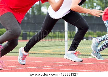 Three girls race each other sprinting at high school track and field practice outside on a red track